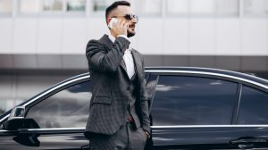 Business man by the car talking on the phone